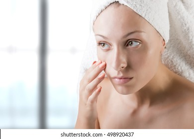 Woman with a towel wrapped around her head checking her skin
