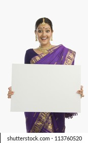 Woman in traditional Assamese dress holding a blank placard and smiling