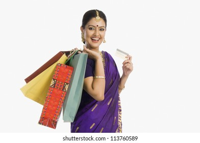 Woman in traditional Assamese dress holding shopping bags with a credit card and smiling