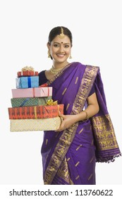 Woman in traditional Assamese dress holding gifts and smiling