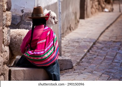Woman in traditional clothes with lama sitting on stone in Cuzco - Peru