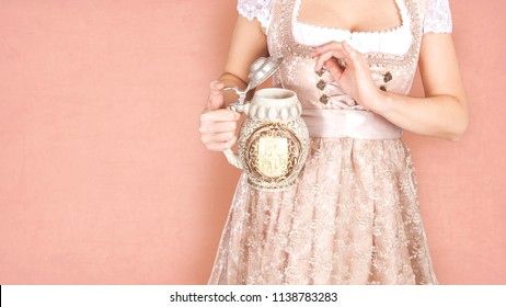 Woman with traditional cup of beer in front of her decollete, wearing dirndl traditional german dress