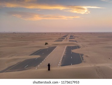 woman in a traditional emirati dress looking at abandoned sand covered desert road near Dubai