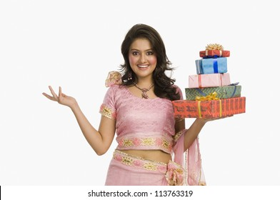 Woman in traditional Indian dress holding gifts and smiling