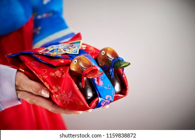 Woman in traditional Korean costume and holding wooden bird carving craft