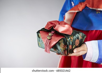 Woman in traditional Korean costume holding embroidery wrapping cloth