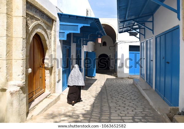 A woman in traditional Muslim clothing goes through the Old town of Sousse. Tunisia. May 6, 2016.