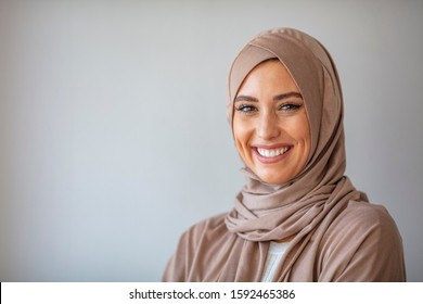 Woman in traditional Muslim clothing, smiling. Beautiful woman headshot looking at camera and wearing a hijab. Arabian woman with happy smile. Strict formal outfit and elegant appearance. Islamic