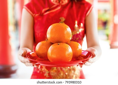 Woman in traditional red qipao dress worshipping god with oranges as an offering during Chinese new year season