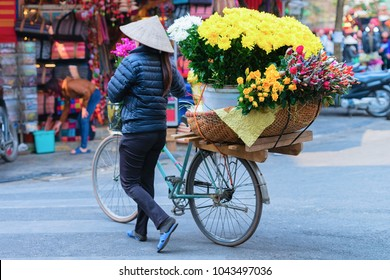 Woman in traditional vietnamese hat on bicycle selling flowers in the street market in Hanoi, Vietnam