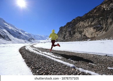 Woman trail runner cross country running in winter nature