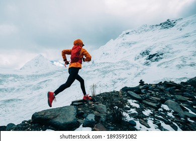 Woman trail runner cross country running up to winter snow mountain top - Shutterstock ID 1893591082