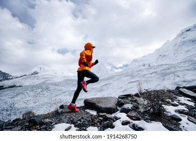 Woman trail runner cross country running up to winter snow mountain top