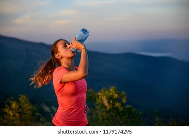 Woman trail runner drinking water from the plastic bottle in the mountains