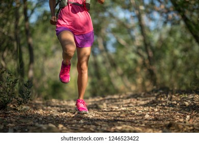 Woman trail runner running in forest trail