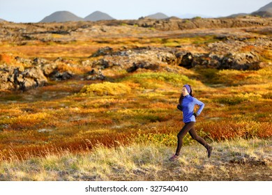 Woman trail runner running in mountain landscape. Female runner in warm winter and fall outfit jogging cross country outdoors in beautiful nature.