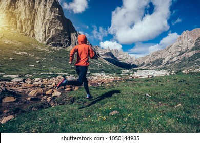 woman trail runner running on beautiful mountains