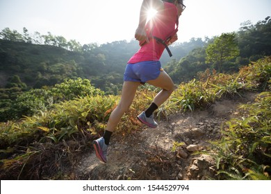 Woman trail runner running up on mountain slope in tropical forest