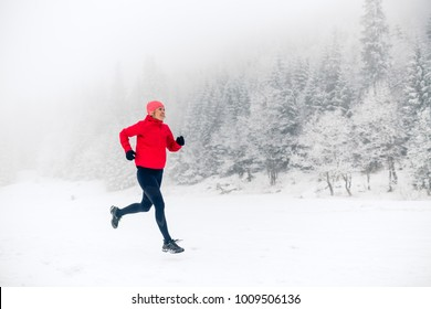 Woman trail running on snow in winter mountains and forest. Sport, fitness inspiration and motivation. Young happy girl athlete working out on snow, winter day. Female runner jogging outdoors.
