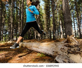 Woman trail running in the woods and jumping over logs while on extreme outdoor fitness training in forest.