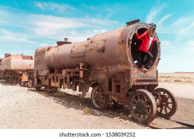 Woman at Train Cemetery in Bolivian Salt Flats, with salty desert and blue sky background. Shot in Salar de Uyuni. Rusted, waste, abandoned, locomotive graveyard, railroad concepts. Tourist attraction