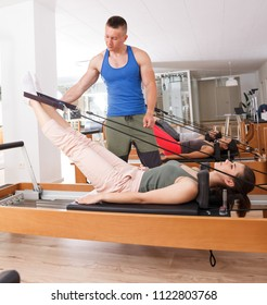 woman with a trainer in gym with modern exercise equipment