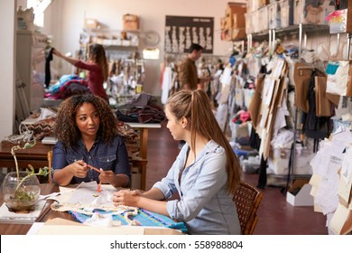 Woman training apprentice at a clothes manufacturing studio