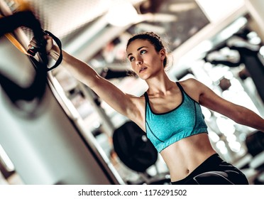 Woman training arms with trx fitness straps in the gym doing push ups train upper body chest shoulders pecs triceps.