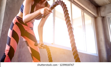 Woman training with battle rope in cross fit gym, Battle ropes session. Attractive young fit and toned sportswoman working out in functional training gym doing cross-fit exercise with battle ropes.