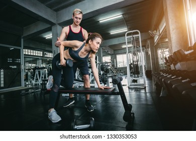 woman and Training doing exercises with dumbbell in gym