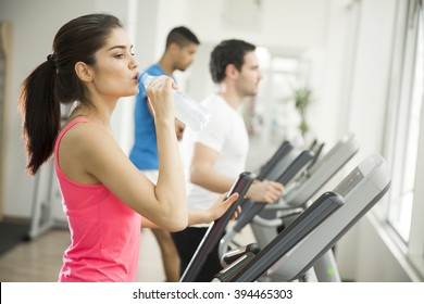 Woman training and drinking water in the gym