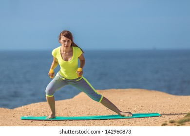 Woman training with dumbbells on the beach. Summer work out, fitness and exercising with weights outdoor. Caucasian sport girl training hard.