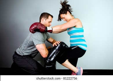 Woman training to fight with a man in a gym.