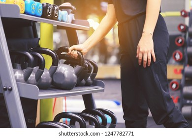 Woman training hand holding kettlebell for burn fat in the body in the sport gym, Healthy lifestyle and sport concept