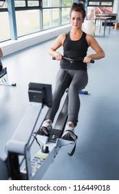 Woman training hard on row machine in gym