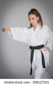 Woman training in judo cloths with black belt, striking a fist punch.