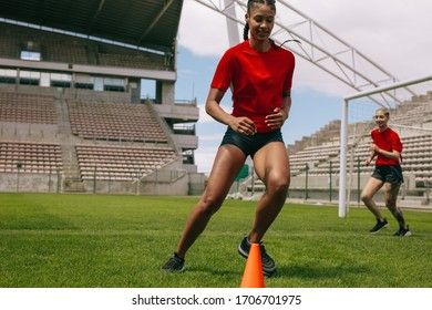 Woman training on football field. Young soccer player running around cones in football field during practice.
