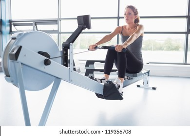 Woman training on row machine in gym