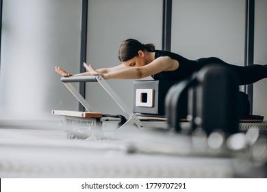 Woman training pilates on the reformer