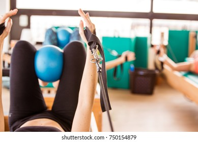 Woman training pilates on reformer apparatus (equipment)