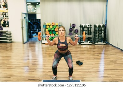 Woman training shoulder in gym lifting weights