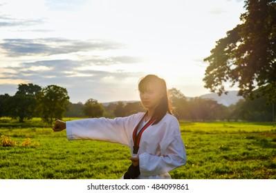 Woman training taekwondo sunset.Photos is backlit