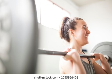woman training with weight bar near the window