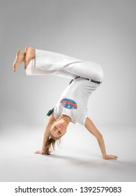 Woman trains capoeira in studio on white background. The woman does the fighting element of capoeira - concept about people, lifestyle and sport.