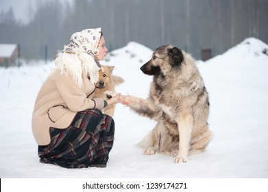 Woman trains Caucasian Shepherd and yard dog on a snowy ground in the park