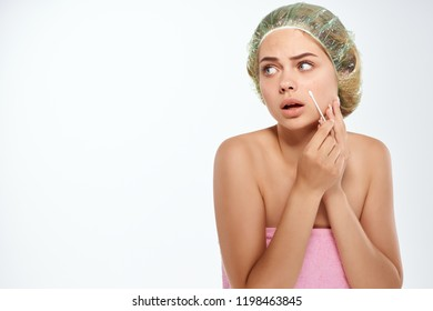 woman transparent hats holding a cotton bud near face