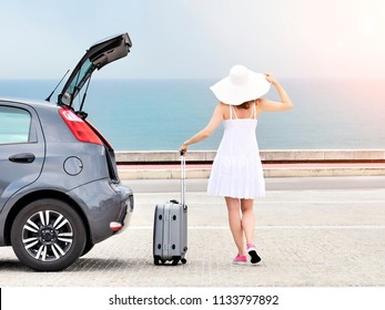 Woman with travel bag standing near hatchback car