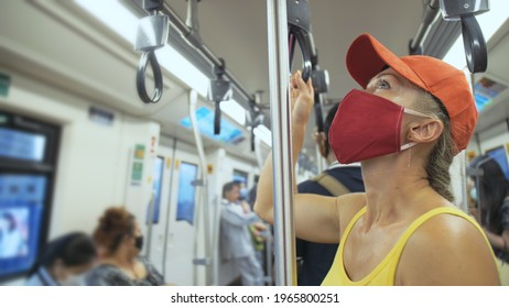 Woman travel caucasian ride at overground train airtrain with wearing protective medical mask. Girl tourist at airtrain with respirator. People mask.