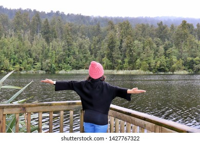 Woman travel influencer enjoying happiness at wander trip - Wanderlust vacation concept with young adventure girl tourist wanderer on excursion in New Zealand - Warm filter
