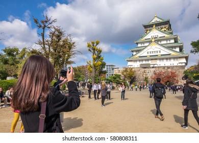 woman travel to Osaka castle Japan taking photo of Osaka castle